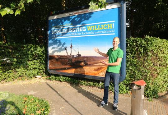 """Merlin Praetor vor Werbeplakat zur Aktion """"Atomausstieg Willich"""""""